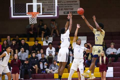 Cheyenne's Glenn Taylor (5) shoots over Faith Lutheran's Azavier Johnson (5) and ...