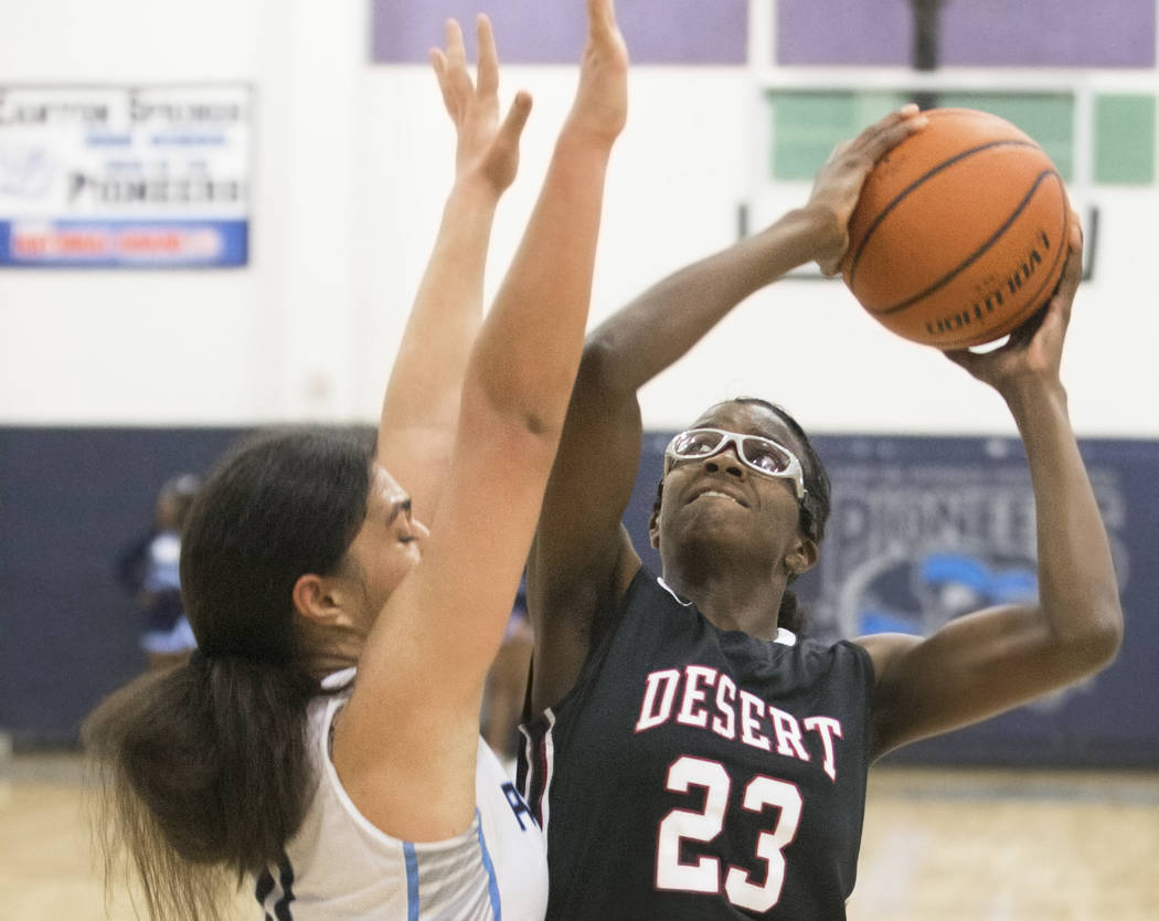 Desert Oasis junior center Desi-Rae Young (23) shoots over Canyon Springs junior forward Jea ...