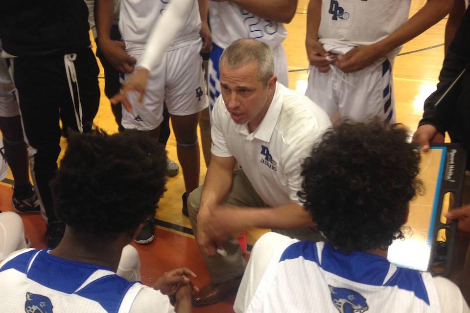 Desert Pines coach Mike Uzan talks to his team between quarters of the Jaguars' 84-67 ...