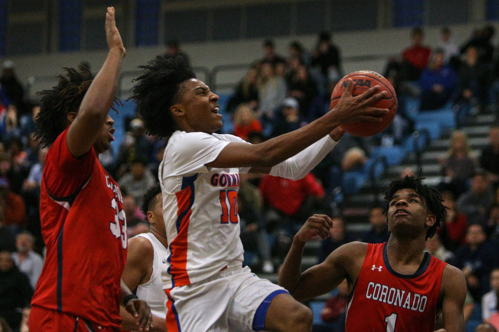 Bishop Gorman's Zaon Collins (10) jumps up to take a shot while being guarded by Coron ...
