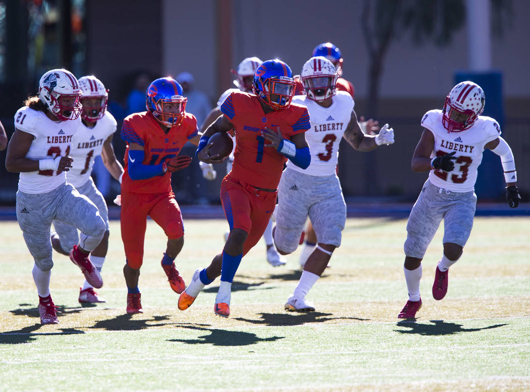 Bishop Gorman's Micah Bowens (1) breaks past Liberty defenders for a touchdown during ...