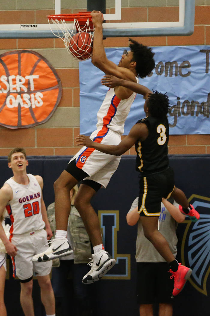 Bishop Gorman's Isaiah Cottrell (0) goes up for a dunk under pressure from Clark&#8217 ...