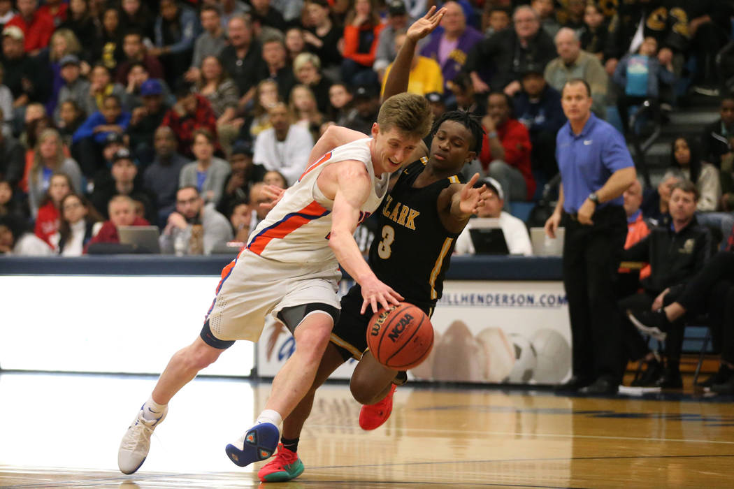 Bishop Gorman's Noah Taitz (20) drives the ball to the hoop under pressure from Clark& ...