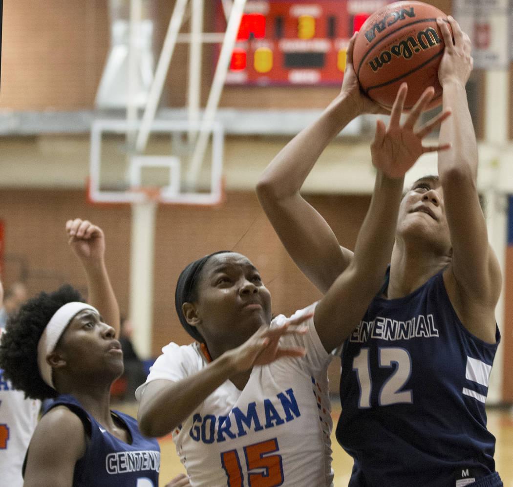 Centennial junior Aishah Brown (12) grabs a rebound over Bishop Gorman freshman Asya Bey (15 ...