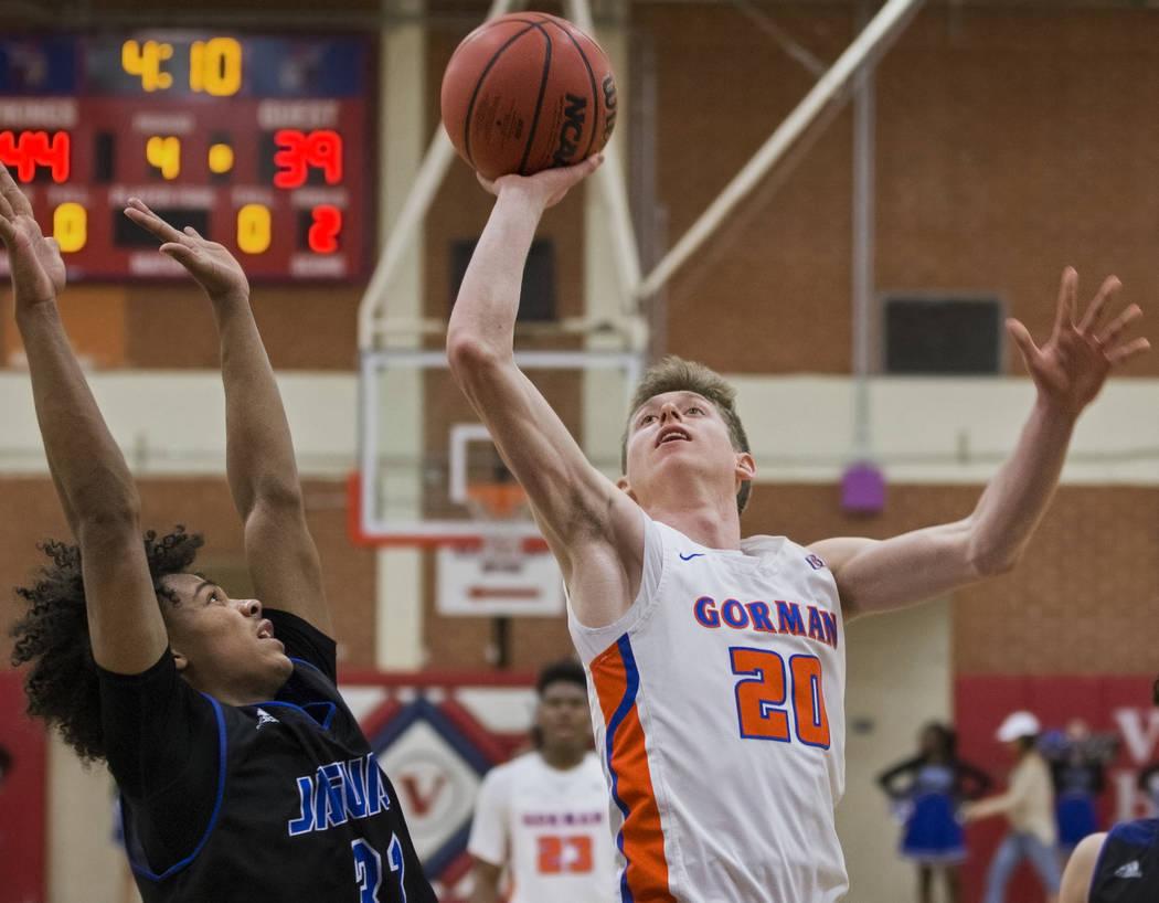 Bishop Gorman senior guard Noah Taitz (20) drives past Desert Pines freshman Jamir Stephens ...
