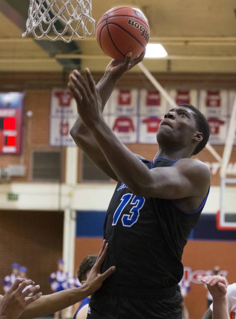 Desert Pines junior Darnell Washington (13) shoots a jump hook over Bishop Gorman defenders ...