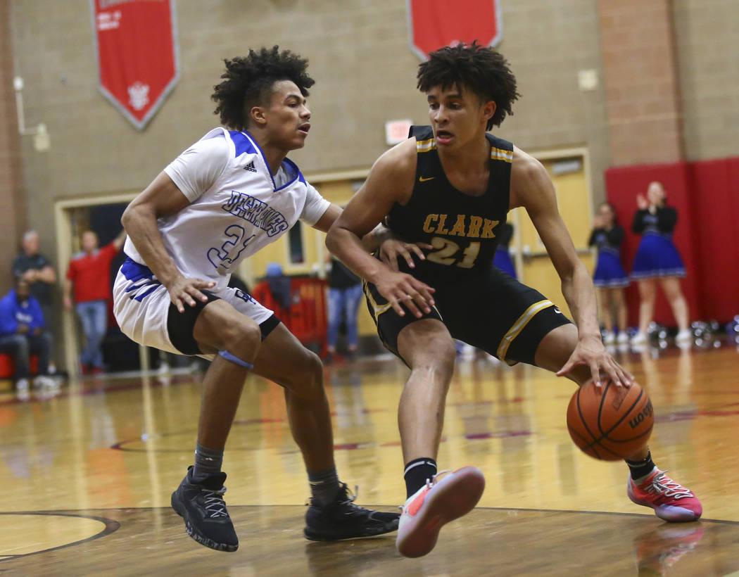 Clark's Jalen Hill (21) moves the ball around Desert Pines' Jamir Stephens (33) ...