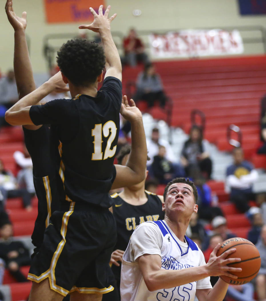 Desert Pines' Roland Gates (35) looks to shoot past Clark's Cameron Kimble (12) ...