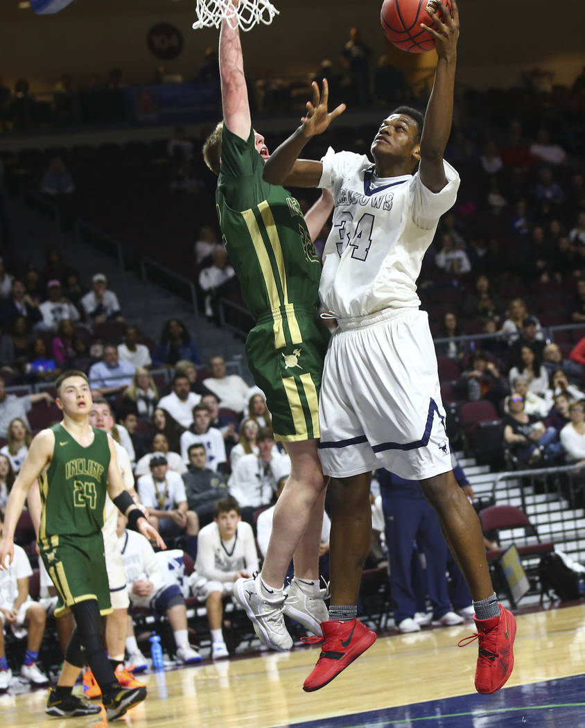 The Meadows' Obinna Ezeanolue (34) goes to the basket against Incline guard Liam Nolan ...
