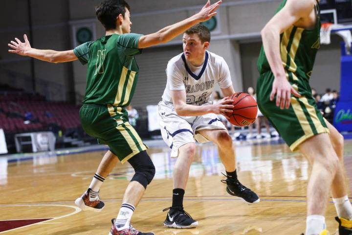 The Meadows guard Allen Fridman (24) moves the ball around Incline guard Johnny Redfern (11) ...