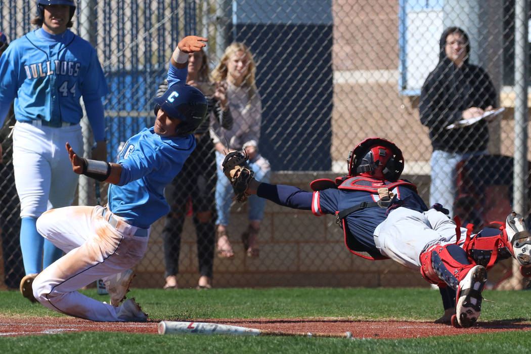 Centennial's Anthony Martinez, left, avoids a tag from Liberty's catcher James K ...