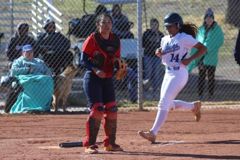 Centennial's Maddie Kallfelz (14) runs home for a run after a hit by Tatum Huntly (9) ...
