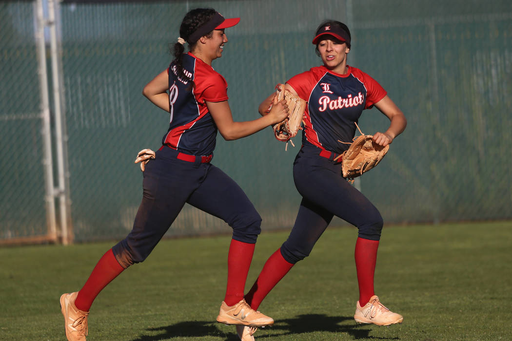 Liberty's Shelby Carvalho (13), left, and Maddison Hamilton (12), run to the dugout af ...