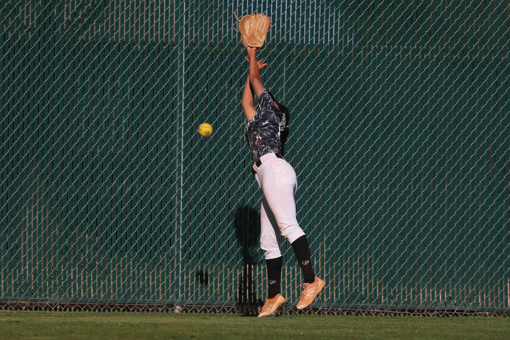 Desert Oasis Paisley Garcia (17) misses the ball to allow a hit by Liberty in the softball g ...
