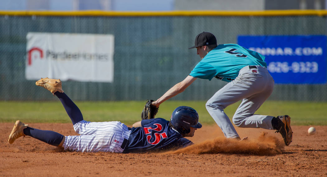 Coronado's Thomas Planellas (25) dives safely back to first base after errant throw to ...
