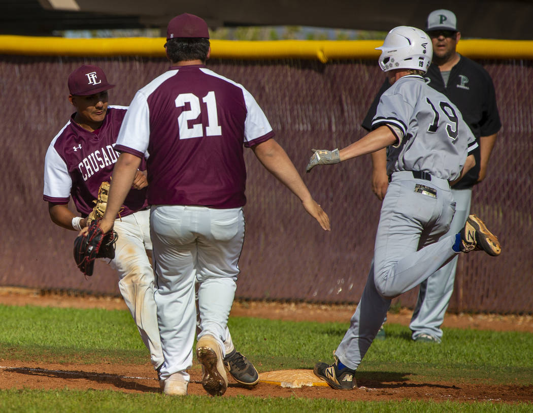 Faith Lutheran's Jacob Ortega (8) gets back to first base for the out before Palo Verd ...