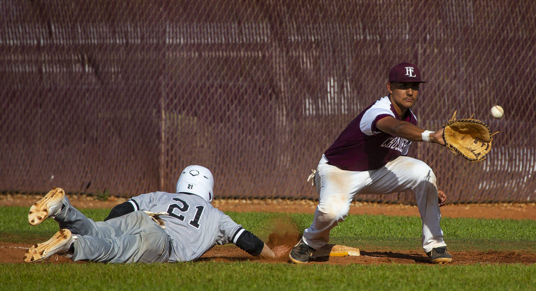 Palo Verde's Josiah Cromwick (21) dives back to first base ahead of a throw to Faith L ...