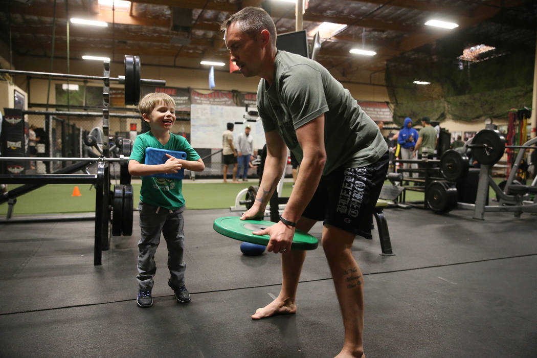 Military veteran Chris Jachimiec, right, works out as his son Cylas, 5, looks on, during a Merg ...