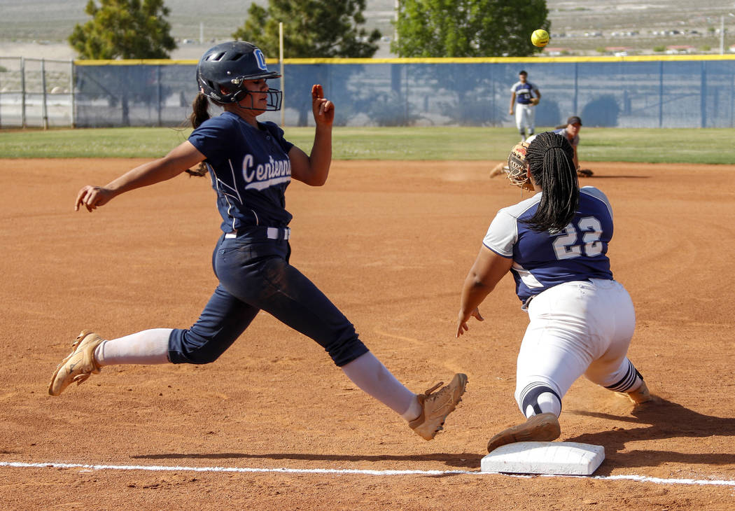 Centennial outfielder Abby Hanley (12) runs safely into first base as the ball is thrown to ...
