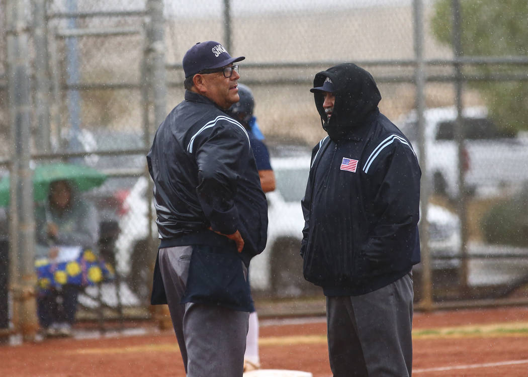 Umpires talk as rain comes down in the first inning of a softball game. (Chase Stevens/Las V ...