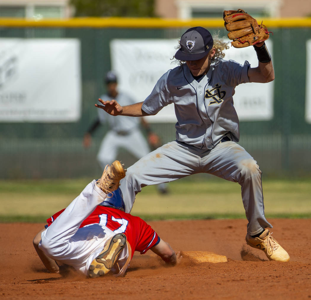 Liberty's Ethan Safier (17) dives back to second base below Spring Valley's Chas ...