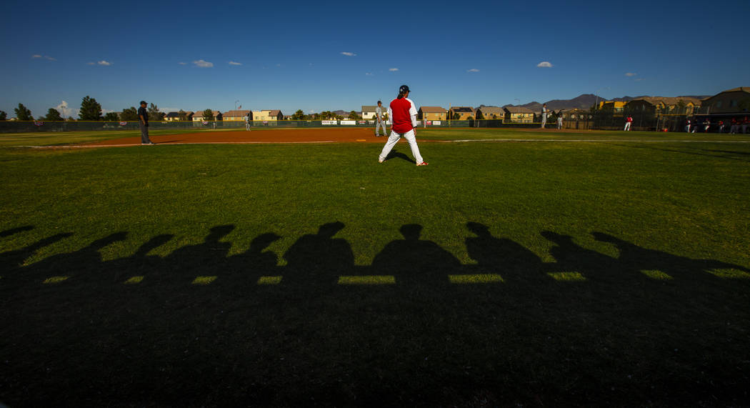 Spring Valley players are silhouetted behind Liberty head coach Rich Ebarb during the first ...