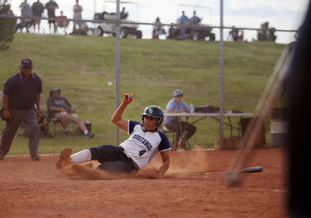 Shadow Ridge High School's Shea Clements (4) slides to make home base against Centenni ...