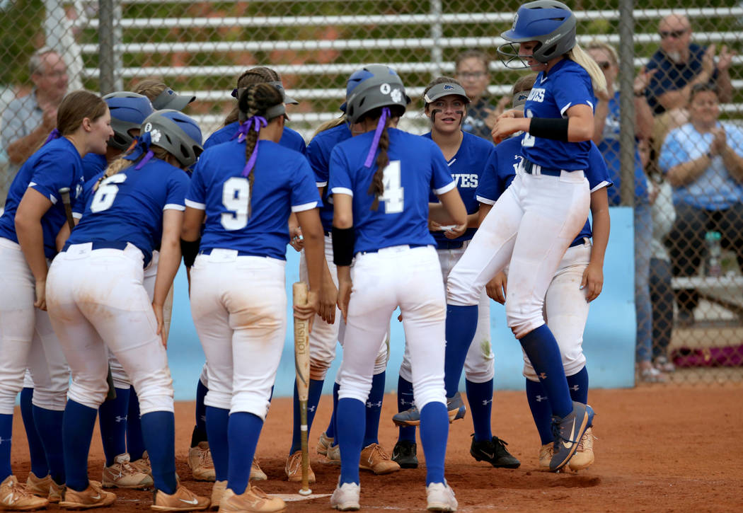 Basic's Sierra McClean (12) hops onto home plate with her teammates in the fourth inni ...
