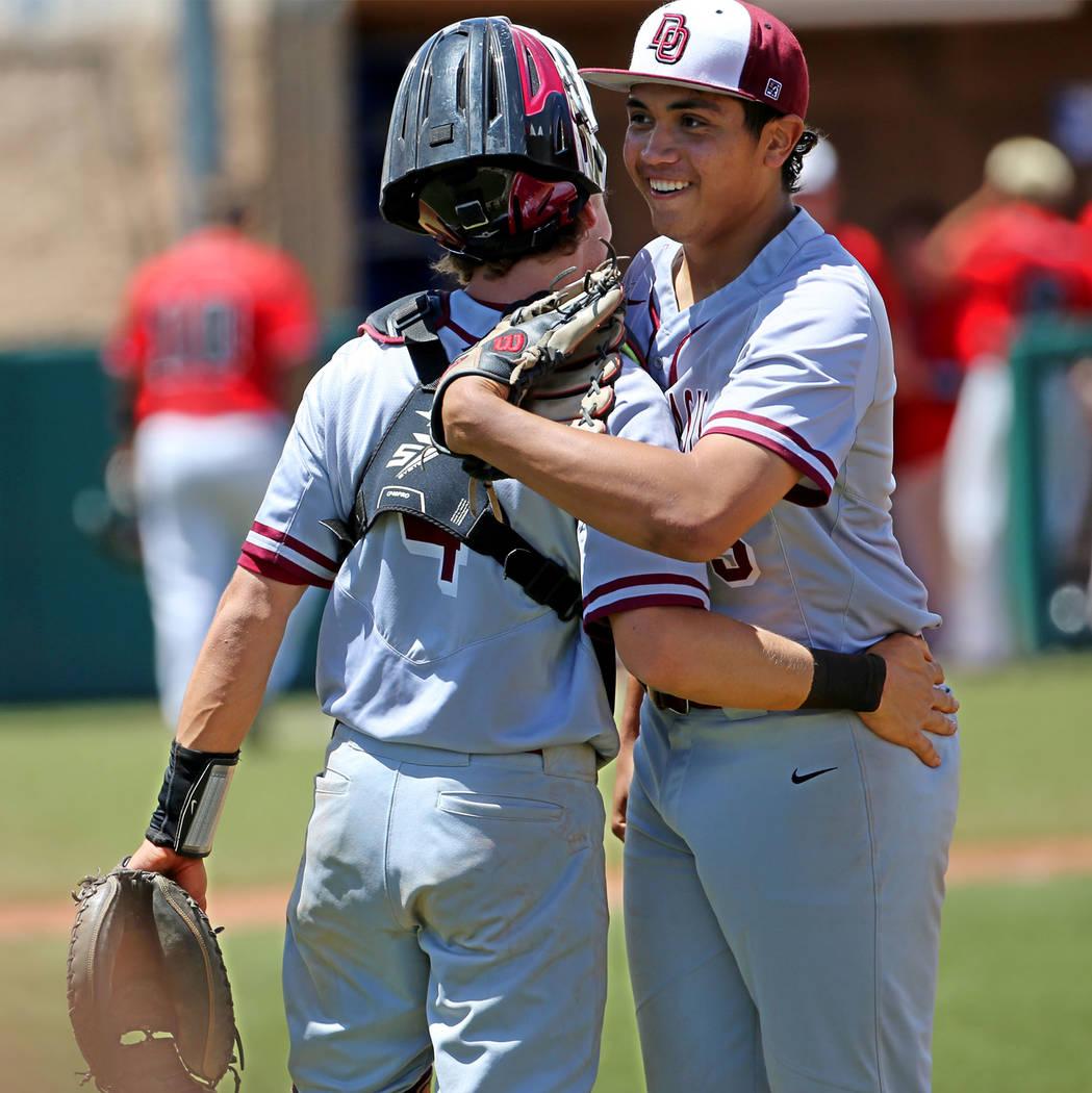 Desert Oasis' pitcher Aaron Roberts (25), right, embraces catcher Parker Schmidt (4) ...