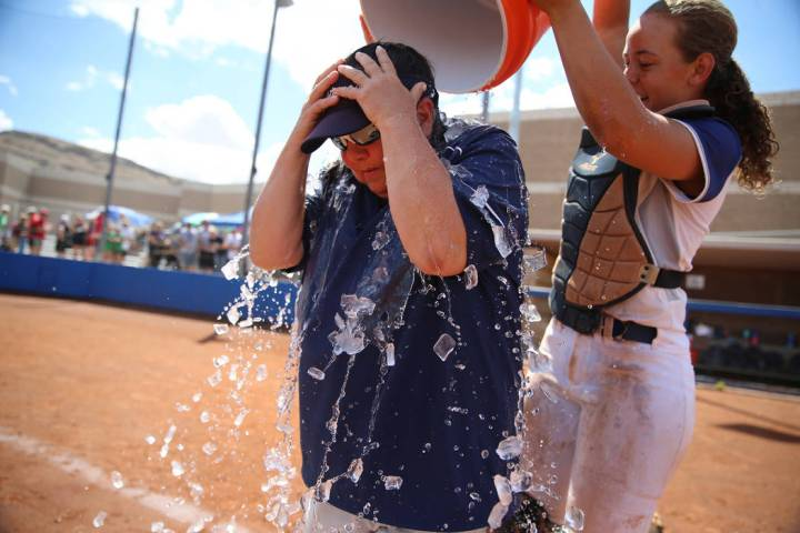 Shadow Ridge's Caitlyn Covington (3) dumps a bucket of ice water on head coach Julia M ...