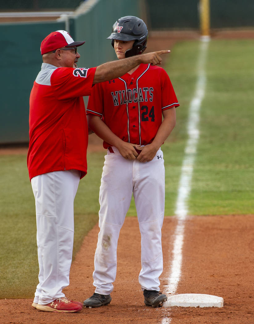 Las Vegas head coach Sam Thomas counsels his runner Brady O'jeda (24) at third base ve ...