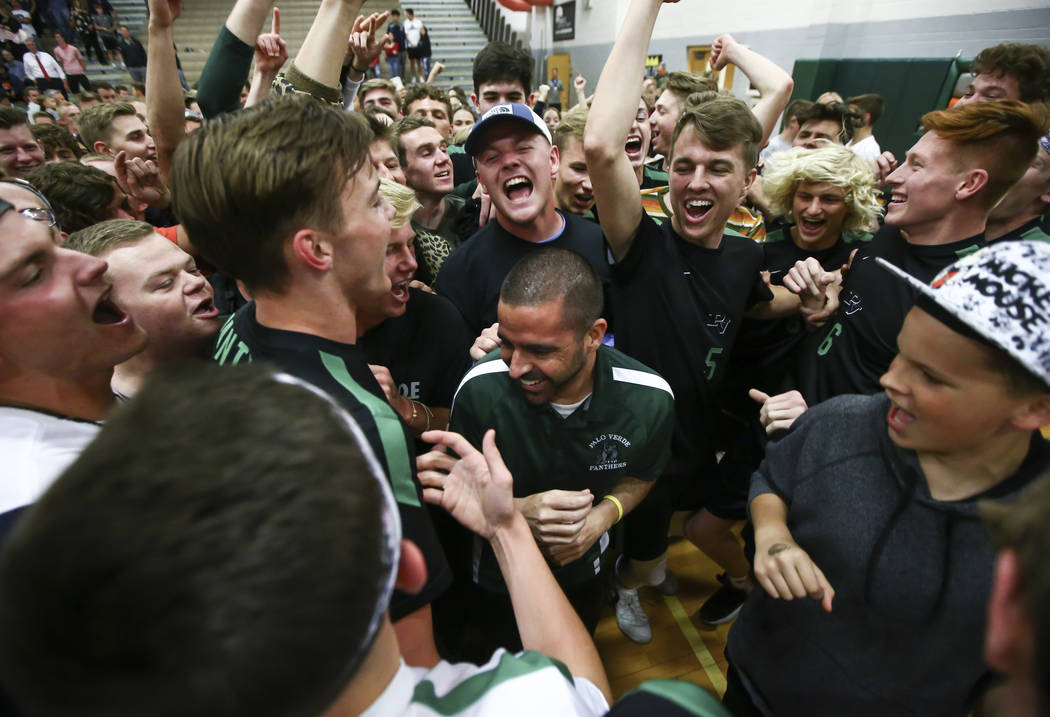 Palo Verde students and players celebrate their victory with head coach Phil Clarke, center, ...