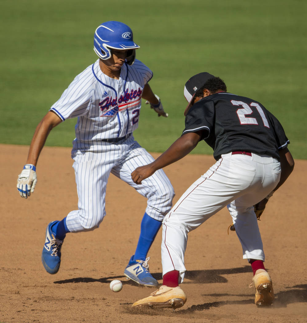 Reno's Skylar Hales (24) scurries safely back to first base after a bad throw to Deser ...