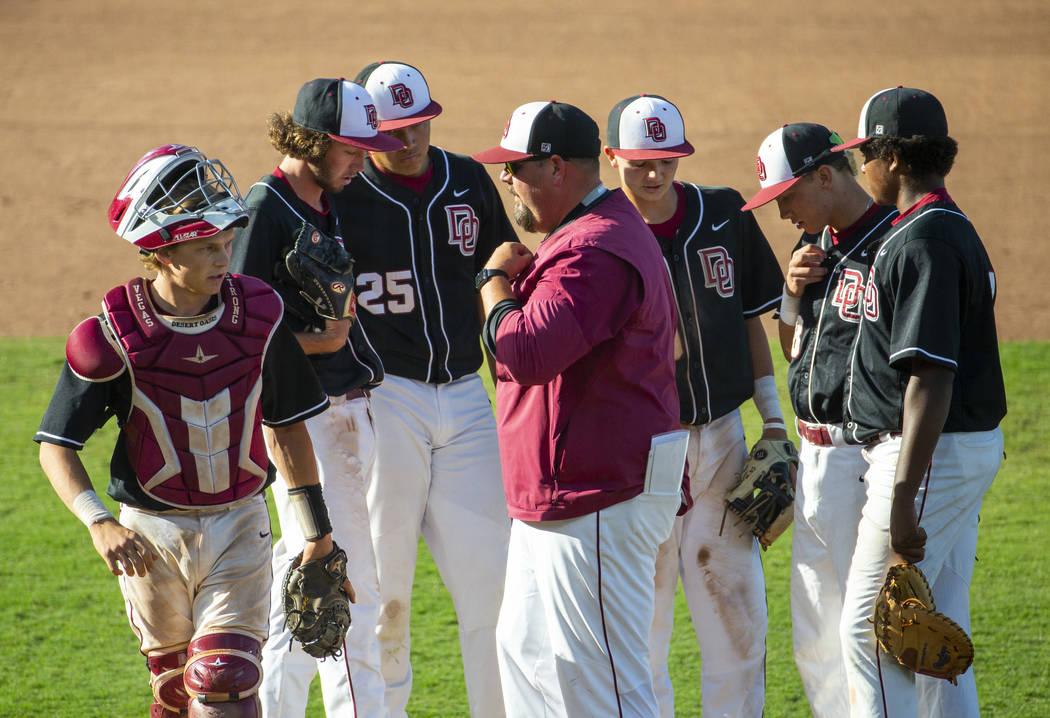 Desert Oasis' players come together on the mound with their coach versus Reno during t ...