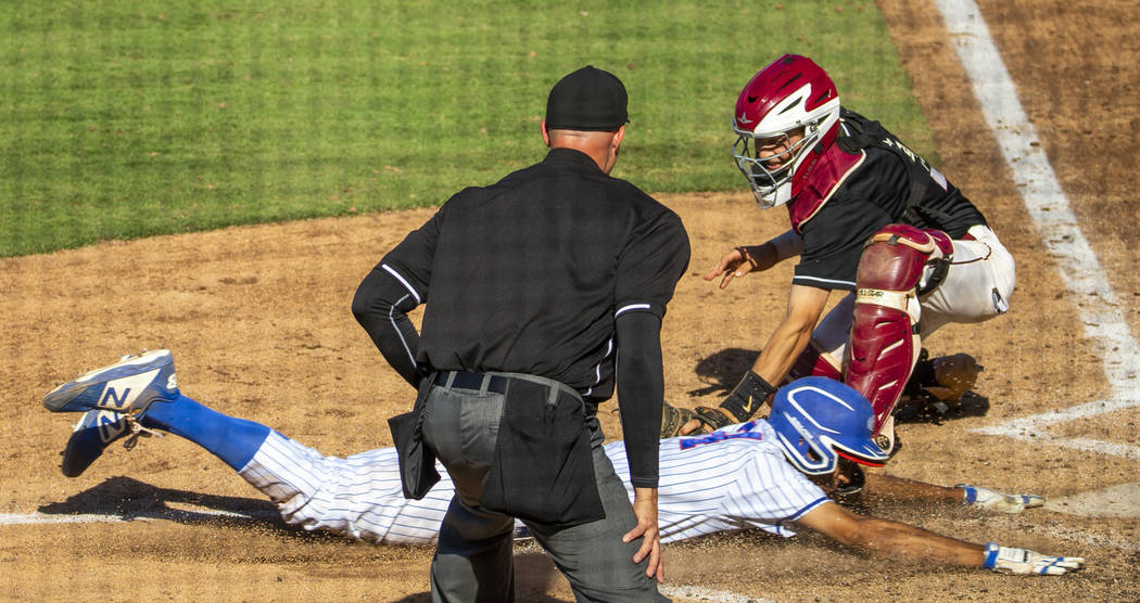 Reno's Skylar Hales (24) just beats the tag at home plate by Desert Oasis catcher Park ...