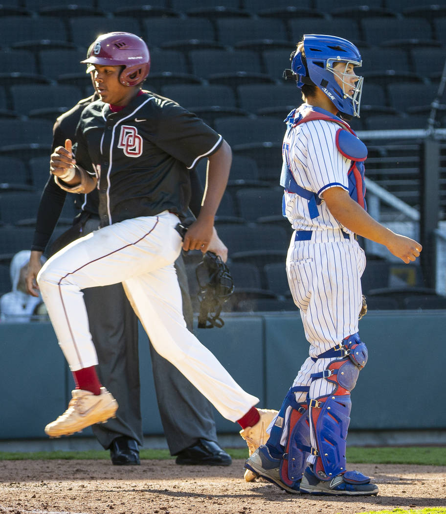 Desert Oasis' Jacob Walsh (21) scores as Reno catcher Lane Oliphant (28) waits for the ...