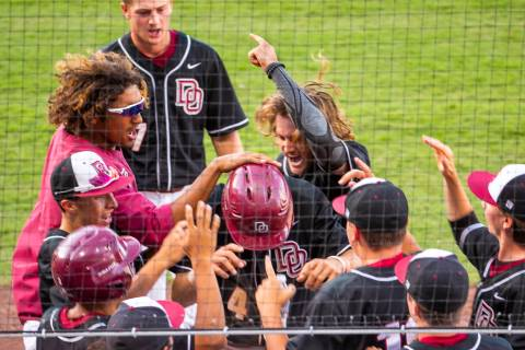 Desert Oasis players congratulate Parker Schmidt (4), center, on another run against Reno d ...