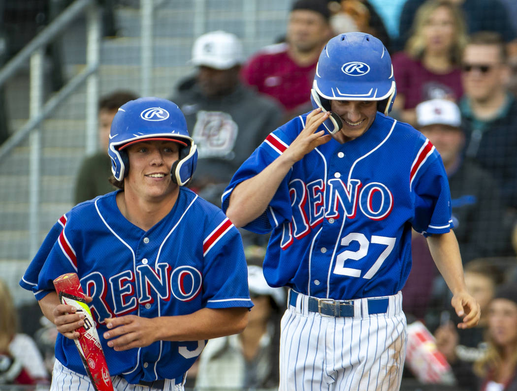 Reno's Drue Worthen (5) and Jake Novacek (27) look to their teammates as they celebrat ...