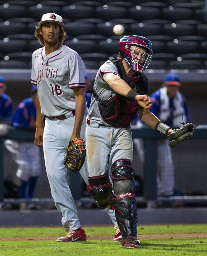 Desert Oasis pitcher DJ Jefferson Jr. (16) looks on as catcher Parker Schmidt (4) makes a th ...