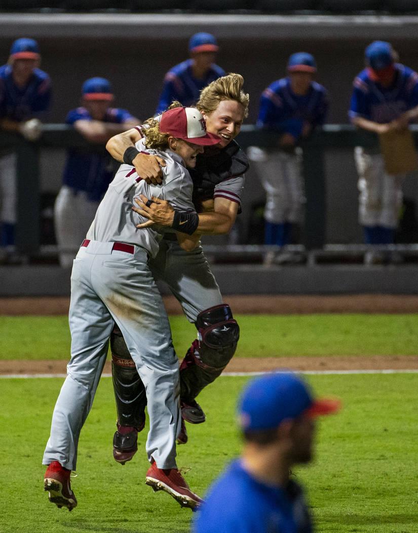Desert Oasis pitcher Josh Sharman (11) celebrates their win with catcher Parker Schmidt (4) ...