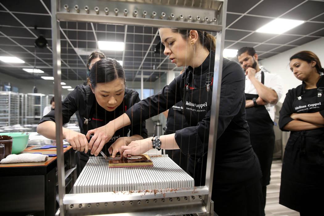 Melissa Coppel helps student Alisha Handelman of New York slice her chocolates at her Las Vegas ...