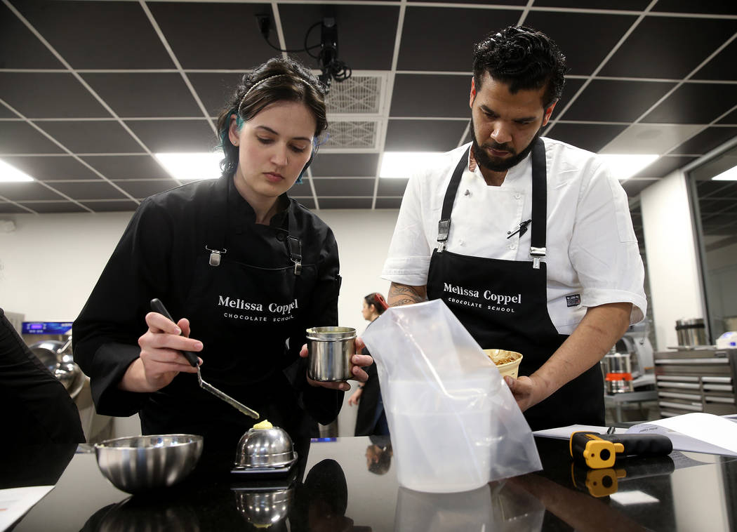 Students Rebecca Travers of Denver and Evin Breton of New York make chocolate creations at Meli ...