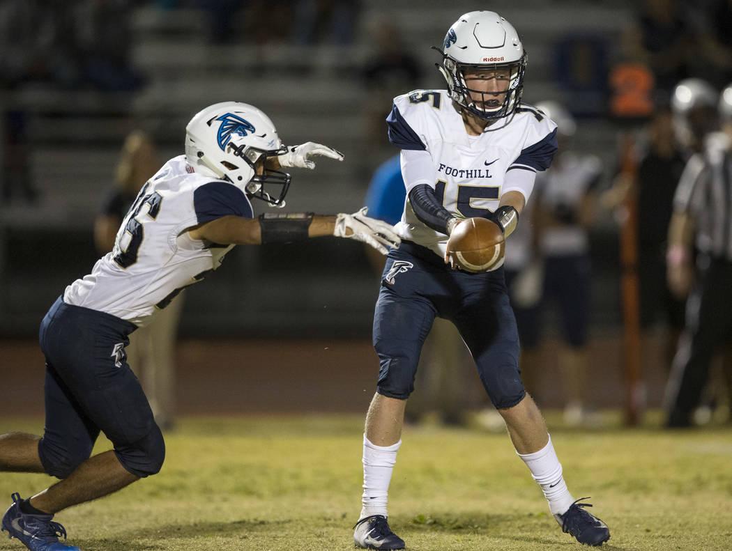 Foothill quarterback Koy Riggin (15) hands off the ball to running back Mario Armendariz (26 ...
