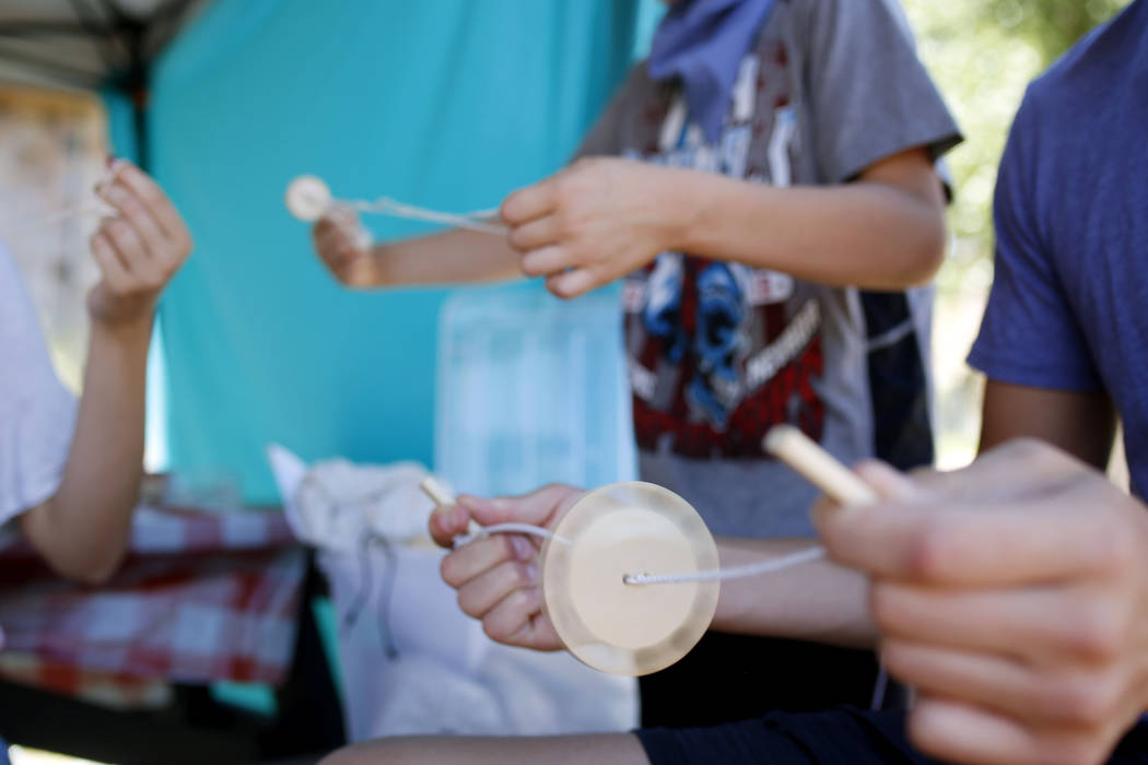 The Talbot siblings make string toys during Pioneer Day at Old Mormon Fort in Las Vegas, Saturd ...