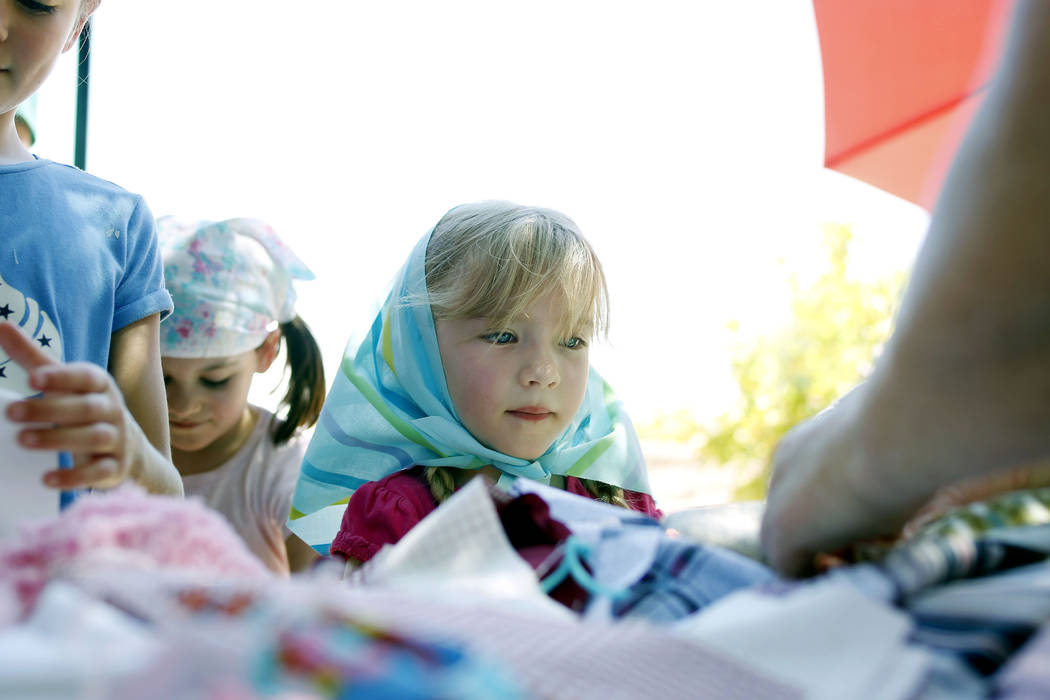 Ava Spencer, 5, watches how to make a pin doll during Pioneer Day at Old Mormon Fort in Las Veg ...