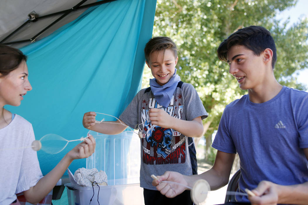 Siblings Cortlin Talbot, 17, left, Ry, 8, and Trayle, 13, play with their string toys during Pi ...