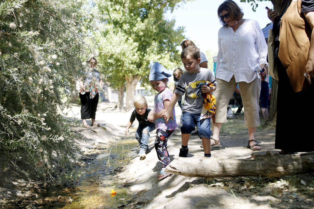 Children watch their plastic ducks used in a duck race float down a river during Pioneer Day at ...