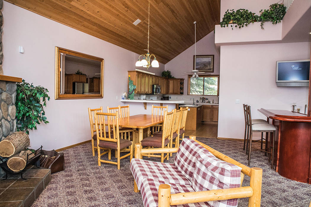 The great room and kitchen is dressed in blond wood log furniture purchased from a furniture ma ...