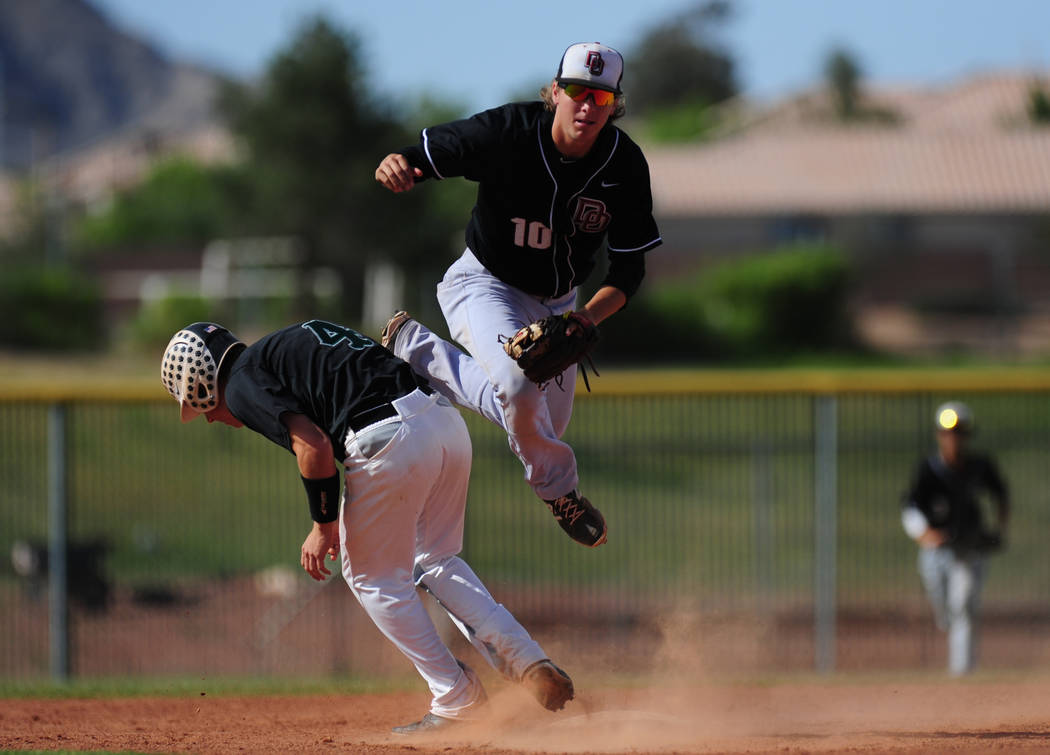 Palo Verde base runner Dylan Orlando (4) interferes with Desert Oasis shortstop Bryson Stott ...