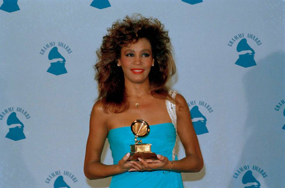 Whitney Houston holds her Grammy in Los Angeles after winning best female pop vocal performance ...